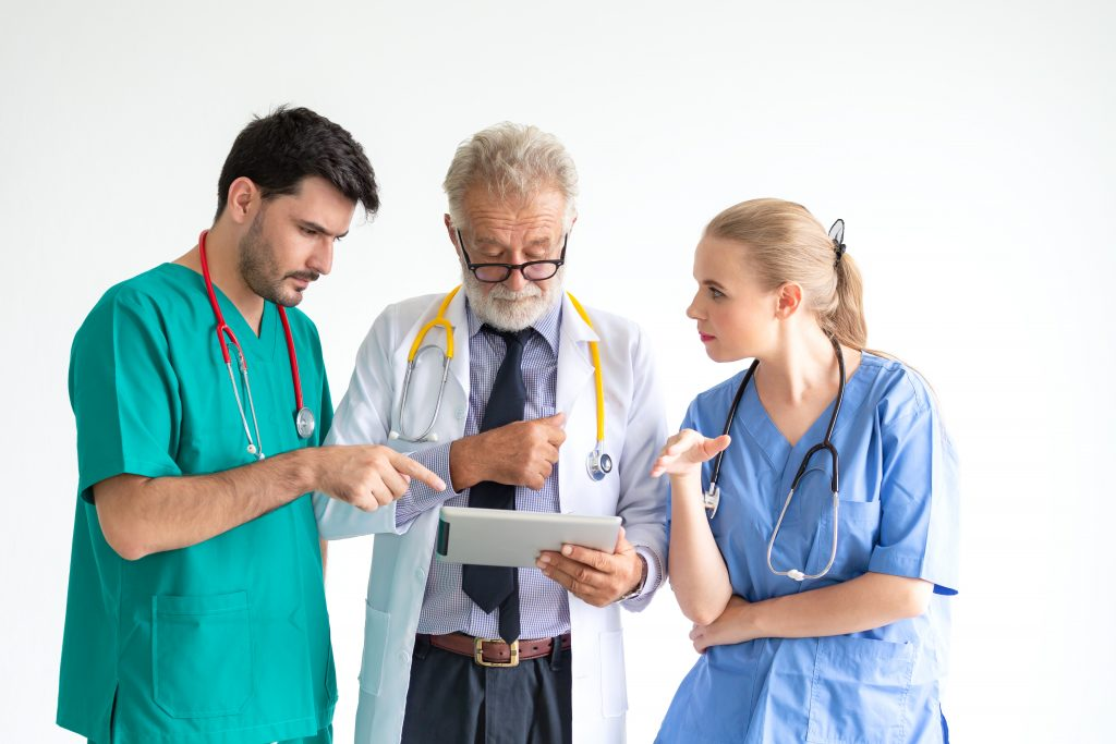 Three doctors consulting over a tablet
